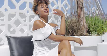 волнение : Young ethnic woman posing in white cocktail dress on white sofa while chilling on luxurious hotel balcony and looking confidently at camera.