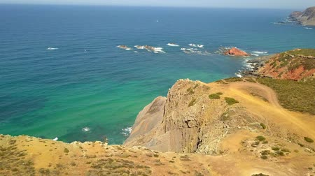 taken : Aerial shot taken from drone of panoramic landscape with cliffs on shoreline of ocean with turquoise water in Algarve, Portugal.