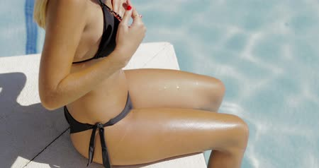 mayo : Young sexual woman in black bikini posing flirty on edge of pool with blue water and looking at camera in bright sunlight. Stok Video