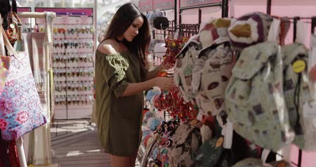 bijouterie : Young wonderful girl in casual outfit posing happily in accessory shop and exploring displays while shopping alone on vacation. Stock Footage