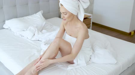 towel : Middle aged beautiful blond woman moisturizes legs after the shower. Using an organic white cream. She is wrapped in towels.