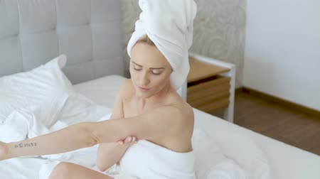 krem : Middle aged beautiful blond woman moisturizes legs after the shower. Using an organic white cream. She is wrapped in towels.