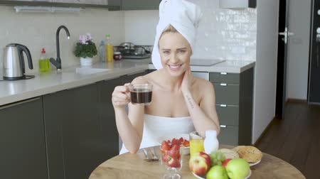 towel : Beautiful woman with towel on head. Sitting next to table in her kitchen, having a healthy breakfast and coffee