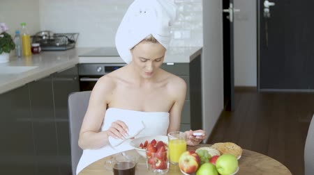 granola : Beautiful middle aged woman sitting in her kitchen in the morning just after shower. She is wrapped in towels. Eating healthy breakfast. Stock Footage