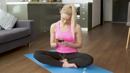 posição : Cute woman sitting on yoga mat in her living room and browsing mobile phone for songs. She listen to the music in earphones.