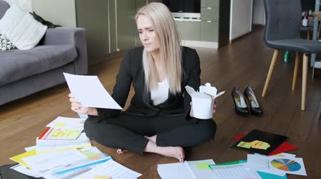 ver : Young caucasian business woman working and eating asian food while sitting on office floor among paper documents Stock Footage