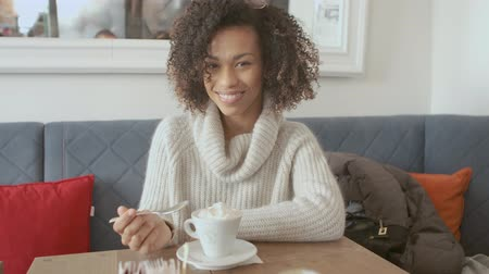 multikulturális : Portrait of beautiful smiling toothy girl student looking at you camera having a relax break at a coffee shop. Multicultural mixed race. Healthy happy life concept