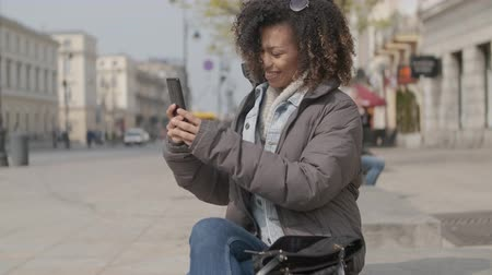 enrolar : Beautiful girl with afro haircut sitting on bench at city street and using mobile phone. Looking at phone screen. Stock Footage