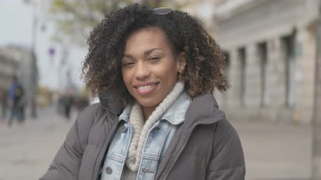задумчивый : Beautiful girl with afro haircut sitting on bench at city street. Looking and smiling to camera.