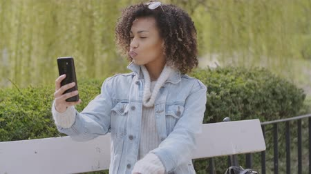 telefonda : Spring or sunny Autumn outdoor portrait of beautiful African American mixed race young woman. She taking a selfie photo with her mobile phone. Stok Video
