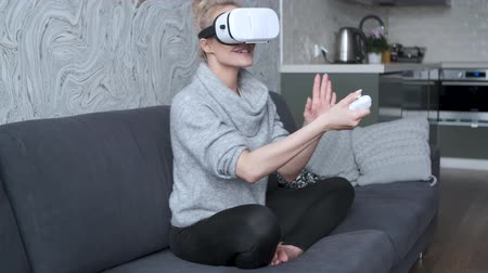 experiência : Young woman watching videos or playing with VR glasses on head sitting on sofa at home.