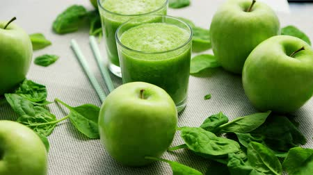 harmanlanmış : Layout of few glasses filled with green smoothie and served on table with green apples and spinach leaves