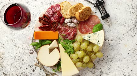 スターター : Assortment of spanish tapas or italian antipasti with meat, ham, olives, cheese, nuts and bread placed on a white rusty table. Top view flat lay with copy space background