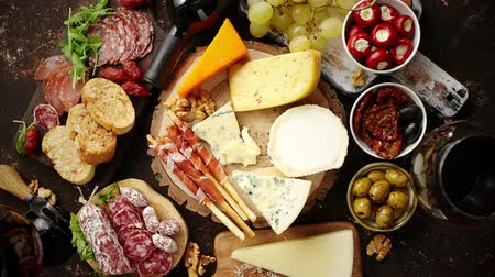 antipasti : Huge assortment of various tasety spanish, french or italian apertizers. Cheese, meat, olives, stuffed peppers, bread, sticks. Placed on rusty dark background. View from above. Stock Footage