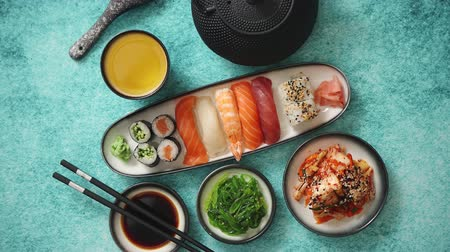васаби : Various sushi rolls placed on ceramic plates. Traditional iron tea pot and green tea in cup. Kimchi and goma wakame salads. Soy souce and chopsticks on sides. Blue background with copy space.