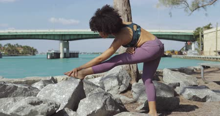 Side view of slim black girl in sportive clothes stretching legs on rocky coast of river with cityscape on background. Stock mozgókép