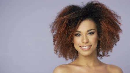 fejlövés : Headshot of cheerful charming young ethnic model with curly hair looking at camera and posing in studio.