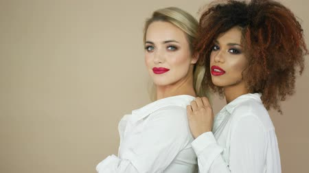 posando : Portrait of cheerful young women with makeup and blode and curly hair looking at camera and posing in studio.
