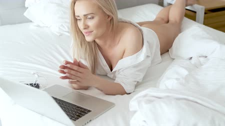 kobiece stopy : A smiling blonde woman lying down the bed in front of her laptop with her legs raised slightly