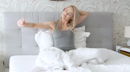 ébredés : Happy young woman enjoying sunny morning on the bed. She stretchs her arms and smiling.
