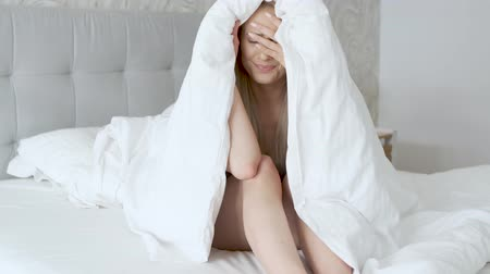 yorgan : Depressed young caucasian model posing on cozy bed wrapped in warm blanket and looking away unwilling to leave for work.