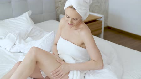 toalhas : Middle aged beautiful blond woman moisturizes legs after the shower. Using an organic white cream. She is wrapped in towels.