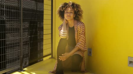 ethnic clothes : Stylish confident African American woman with curls sitting and posing on street against bright yellow wall looking at camera in sunlight