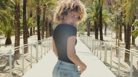koketa : Side view of beautiful relaxed black woman with Afro hairstyle holding hands in pockets of denim shorts smiling at camera against palms Dostupné videozáznamy