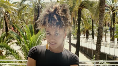 серьги : Portrait of cool young black woman with Afro hairstyle wearing trendy earrings and posing on street smiling at camera in sunshine Стоковые видеозаписи