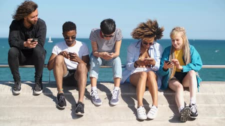 separado : Group of trendy multiracial women and men sitting on waterfront absorbed with mobile phones spending time together in summer time