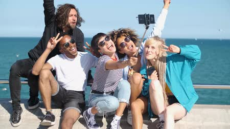 grimacing : Cool young diverse women and men sitting on sea embankment using smartphone and taking selfie while grimacing and having fun