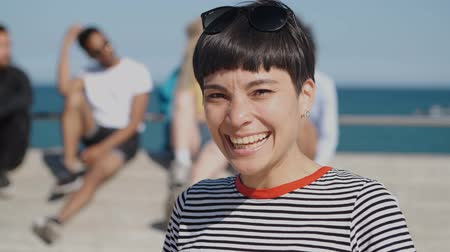 içerik : Portrait of cool young brunette in casual striped t-shirt and sunglasses laughing happily at camera standing on seafront with friends on background Stok Video