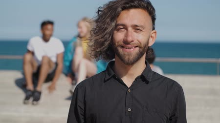 набережная : Crop modern man with beard and long trendy hairstyle wearing black shirt and looking at camera standing on waterfront with friends Стоковые видеозаписи