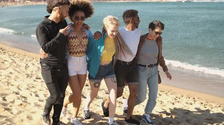 stroll : Group of modern young multiracial women and men in stylish summer clothes embracing while walking on seashore and laughing happily