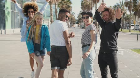 excitação : Back view of happy young multiethnic men and women in trendy clothes having fun and waving with hands at camera on street