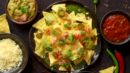 chili : Tasty mexican nachos chips served on ceramic plate with cheese, hot peppers, tomatoes, limes, salsa and guacamole. Placed on dark rusty table. Stock Footage