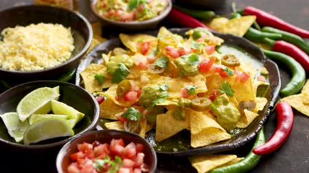 pieprz : Tasty mexican nachos chips served on ceramic plate with cheese, hot peppers, tomatoes, limes, salsa and guacamole. Placed on dark rusty table. Wideo