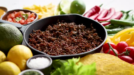 çili : Chili con carne in frying pan on white wooden table. Ingredients for making Chili con carne.Top view. Chili with meat, nachos, tacos, limes, avocado, hot pepper. Mexican Texas traditional dish