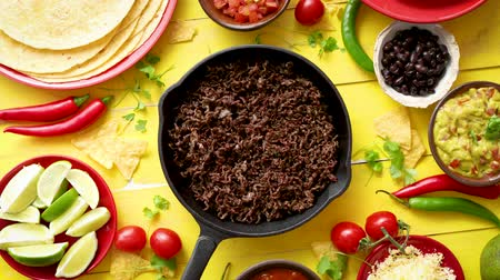 chilli sauce : Various fresh and tasty ingredients for chilli con carne. With meat on iron pan, tortillas, vegetables, cheese, bean. Placed on wooden yellow table