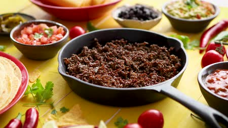taco : Various fresh and tasty ingredients for chilli con carne. With meat on iron pan, tortillas, vegetables, cheese, bean. Placed on wooden yellow table