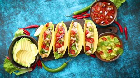 picante : Mexican taco with chicken meat, jalapeno, fresh vegetables served with guacamole and tomato salsa. Latin american food. Placed on blue table.
