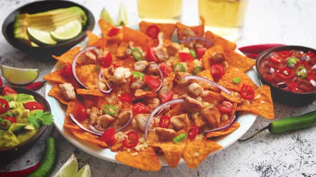 dips : Mexican corn nacho spicy chips served with melted cheese, peppers, tomatoes, beer and side salsas. Stock Footage