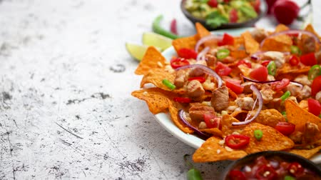 çili : A plate of delicious tortilla nachos with melted cheese sauce, grilled chicken, jalapeno peppers, red onion, tomato, guacamole dip and spicy salsa. With cold sparkling beer.