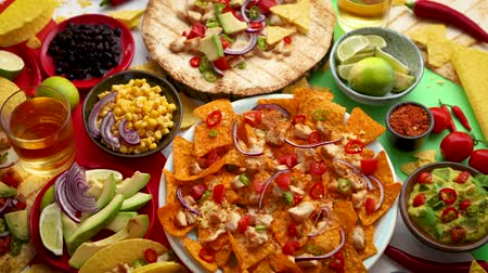 chilli sauce : Various freshly made Mexican foods assortment. Placed on colorful table. With nachos, tacos, tortillas, grilled meat, dips, salsa and vegetables.