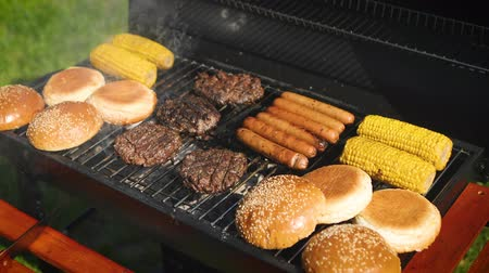 párek v rohlíku : Mixed american barbecue food on hot grill. Hamburgers, hotdogs, corn being grilled. Tasty composition. Outdoor party.