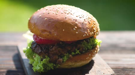 ground meat : Tasty beef burger with, lettuce, onion and tomatoes served outdoor garden on a rusty wooden table Stock Footage