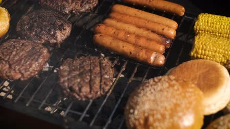 хот дог : Mixed american barbecue food on hot grill. Hamburgers, hotdogs, corn being grilled. Tasty composition. Outdoor party.