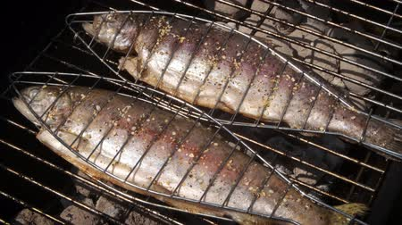 makrela : Tasty whole fishes placed on barbecue grill. Trout with herbs on fire. Aromatic dish in summer outdoor party