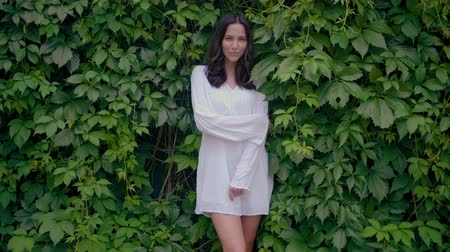 дубленый : Female model in white tunic dress with green leaves on background as a wall. Beautiful caucasian brunette girl in fashionable summer clothes posing in nature.