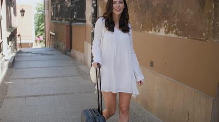 arrasto : Beautiful woman walking with trolley suitcase in small street in the city. Smiling to the camera. Wearing summer time dress.